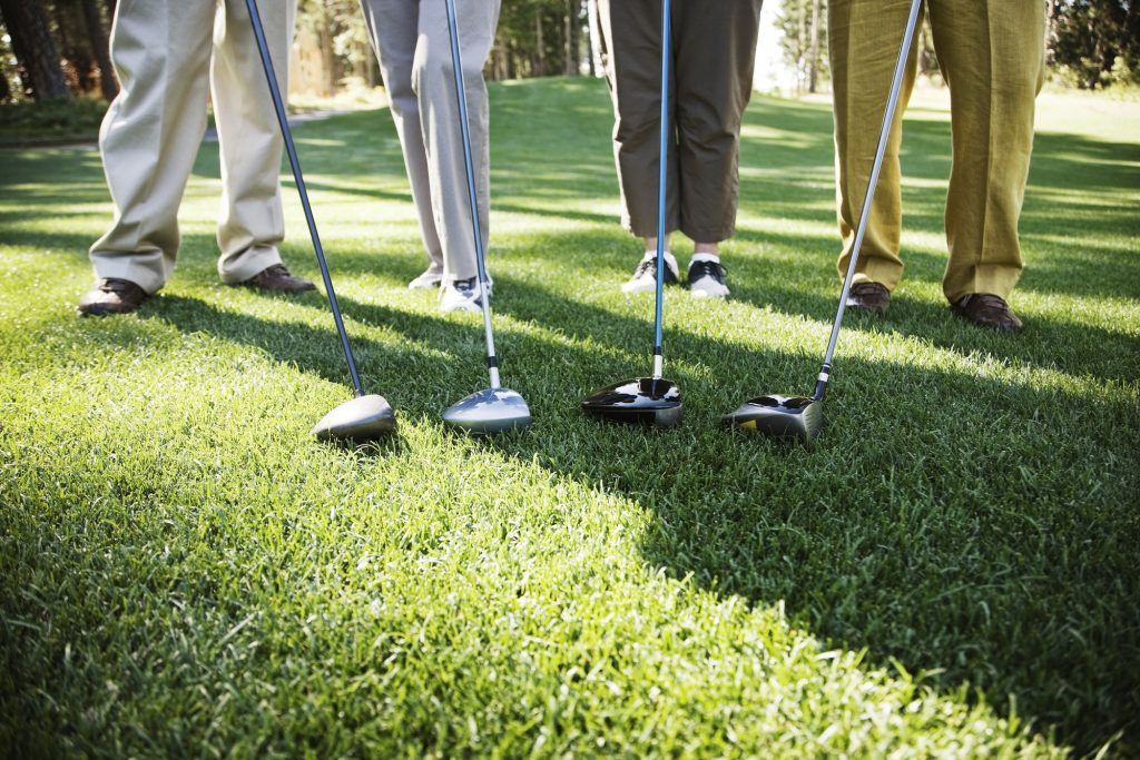 Closeup of the feet of four golfers and the head of their driver clubs.